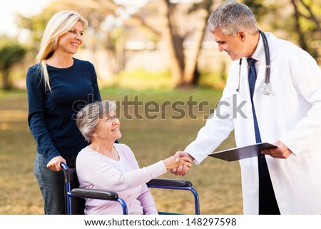 friendly male doctor handshaking with senior patient outdoors - stock photo