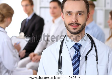 Friendly male doctor on the background with  many patients