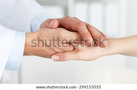 Friendly male doctor's hands holding female patient's hand for encouragement and empathy. Partnership, trust and medical ethics concept. Bad news lessening and support. Patient cheering and support - stock photo