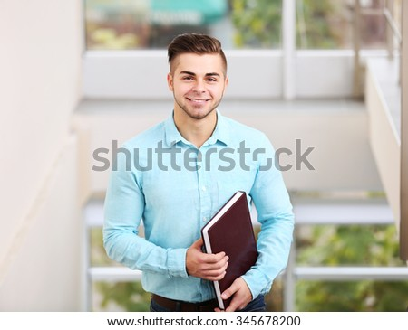 Friendly male estate-agent on light background