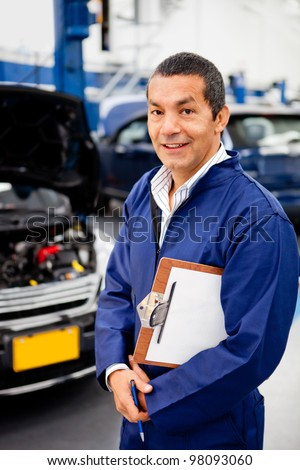 Friendly male mechanic working at a car garage - stock photo