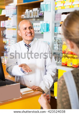 Friendly male pharmacist serving young woman in pharmacy and smiling - stock photo