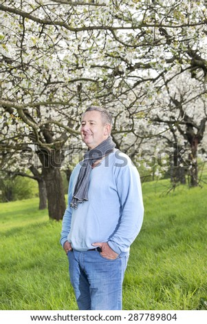 Friendly man in nature under blooming cherry tree - stock photo