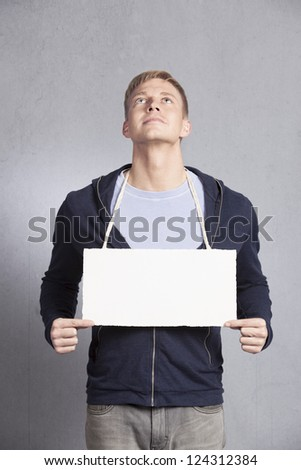 Friendly man looking upwards while presenting white blank signboard with space for text  isolated on grey background. - stock photo