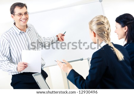 Friendly man standing at whiteboard and pointing at something on it while looking at smart women