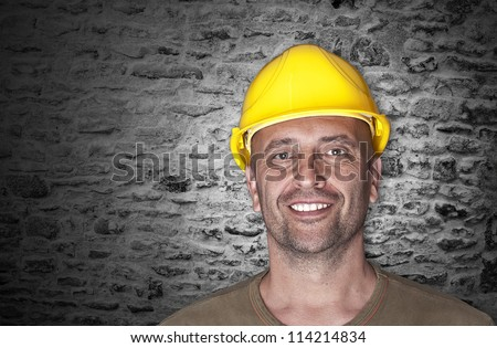 Friendly man with yellow helmet at the building-site - stock photo