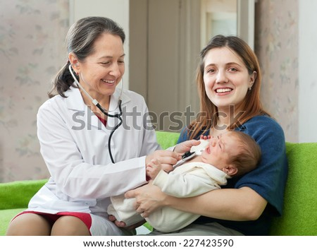 friendly mature children's doctor examining newborn baby on mother's arms with  stethoscop