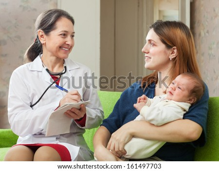 friendly mature pediatrician doctor of prescribes to baby the medication at home