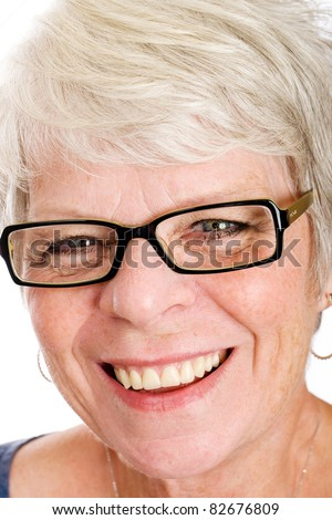 Friendly, mature white haired woman with glasses and a smile. - stock photo