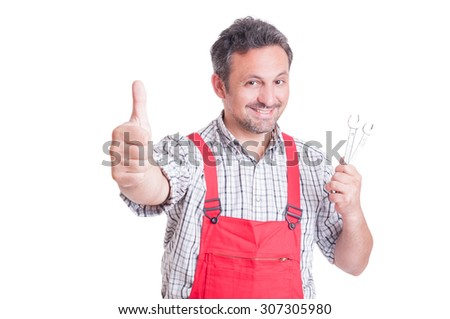 Friendly mechanic holding spanners and showing like gesture isolated on white