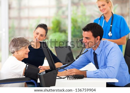 friendly medical doctor taking senior woman's blood pressure - stock photo