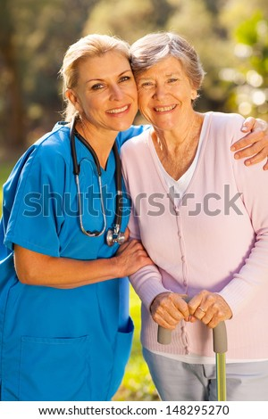 friendly mid age caregiver hugging senior patient outdoors - stock photo