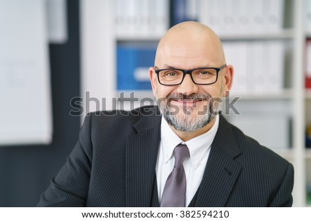 Friendly middle-aged businessman with a goatee and glasses wearing a formal suit sitting in his office smiling at the camera, close up view - stock photo