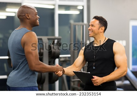 friendly middle aged gym trainer greeting client - stock photo
