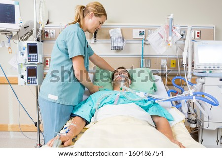 Friendly nurse adjusting patient's pillow in hospital room - stock photo