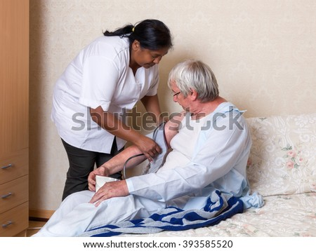 Friendly nurse checking blood pressure of an elderly man in a nursing home - stock photo