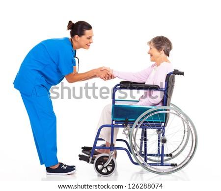 friendly nurse greeting disabled senior patient - stock photo