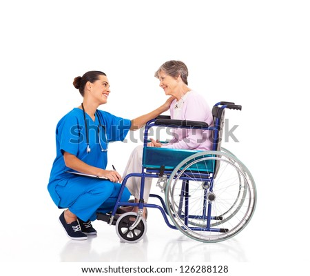 friendly nurse talking to disabled senior patient - stock photo