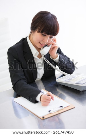 Friendly operator taking notes while answering a call  - stock photo