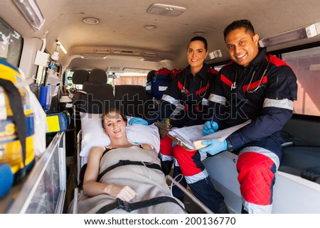 friendly paramedic team and patient inside an ambulance - stock photo