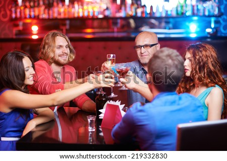 Friendly people toasting with alcoholic drinks at party - stock photo