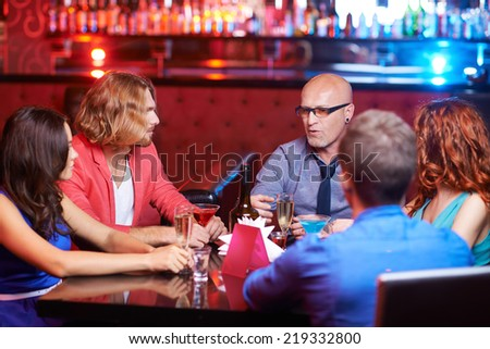 Friendly people with drinks talking at party - stock photo
