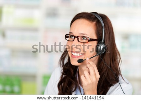 Friendly Pharmacist wearing headset at the drugstore - stock photo