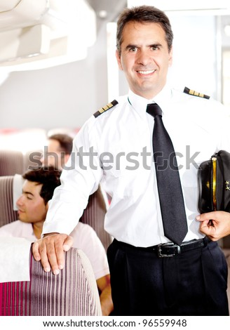 Friendly pilot in the passengers cabin of an airplane smiling - stock photo