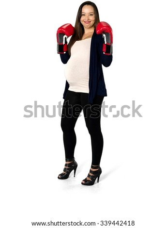 Friendly pregnant young woman with long dark brown hair in casual outfit being in boxing stance - Isolated