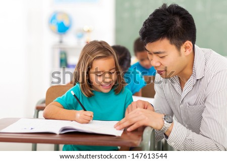 friendly preschool teacher helping little girl with class work - stock photo