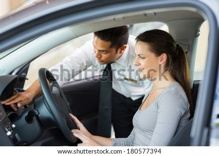 friendly salesman explaining car features to young female customer - stock photo