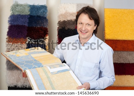 Friendly salesman with fabric and carpet samples in a book in his hands looking at the camera with a smile - stock photo