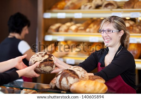 friendly saleswoman in bakery passing bread over the counter - stock photo