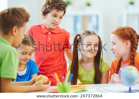 Friendly schoolkids communicating at break - stock photo