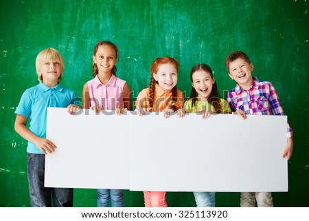 Friendly schoolkids with blank paper standing against blackboard - stock photo