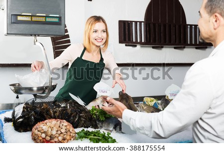 Friendly seller helping customer choosing chilled fish in fish store