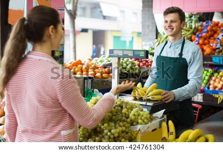 Friendly seller weighing bananas on scale for  woman