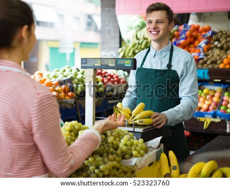 Friendly seller weighing eco bananas on scale for young woman