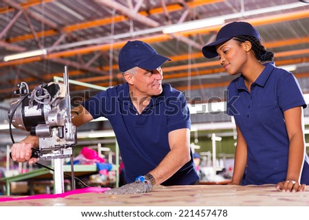 friendly senior cutter teaching young worker cutting fabric - stock photo