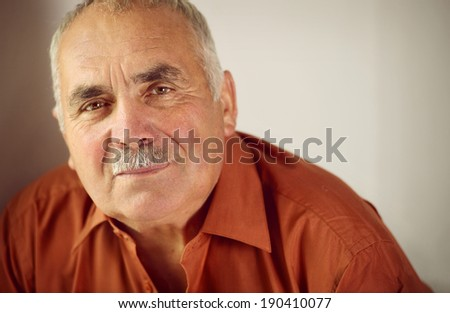 Friendly senior man with a moustache leaning forwards as he looks at the camera with a quiet smile, copyspace on a grey background