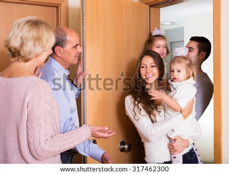 Friendly senior people welcoming dear guests with kids indoor  - stock photo