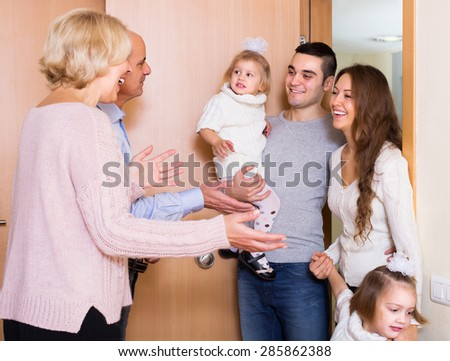 Friendly senior people welcoming dear smiling guests with kids indoor - stock photo
