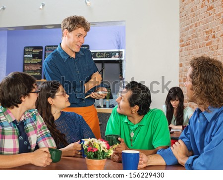 Friendly server taking orders from people in cafe - stock photo