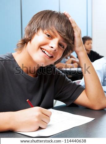 Friendly, smiling adolescent boy in school classroom. - stock photo