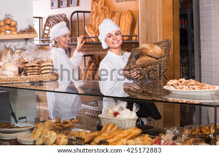 Friendly smiling female bakers selling fresh pastry and loaves in bread section