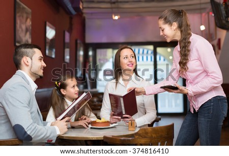 Friendly smiling girl serving family of three at cafe table. Selective focus on girl - stock photo