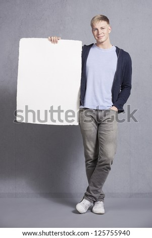 Friendly smiling man holding white blank panel with space for text isolated on grey background. - stock photo