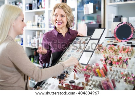 Friendly smiling mature female seller near display with cosmetics in beauty store