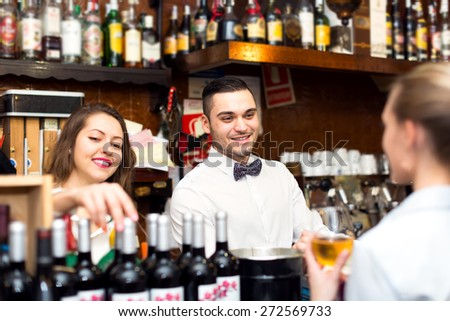 Friendly smiling people working in a popular bar. A barista, bartender and a waitress