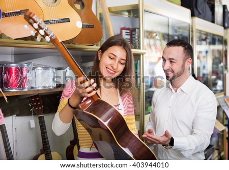 Friendly smiling positive shopgirl helping male client to select guitar in shop